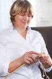 在家编织在轮幅的微笑的中年妇女 免版税库存照片