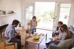 在家聚会两个的家庭 免版税库存图片