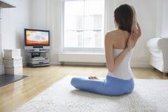 在家舒展胳膊和看电视的妇女 免版税库存图片