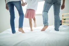 在家花费业余时间的家庭,一起跳跃愉快的家庭在床上 免版税库存照片