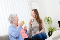 在家花费时间和喝与一个快乐的女孩的愉快的老资深妇女茶 免版税库存图片