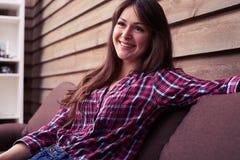 在家花费时间的可爱的女孩,当坐沙发时 免版税图库摄影