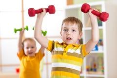 在家行使与哑铃的小孩男孩 健康生活,嬉戏孩子 免版税库存图片