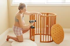 在家装配木婴孩小儿床的年轻白白种人愉快的妇女画象在托儿所 免版税库存图片