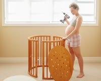 在家装配木婴孩小儿床的年轻白白种人愉快的妇女画象在托儿所 库存照片