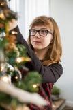 在家装饰圣诞树的十几岁的女孩 库存照片