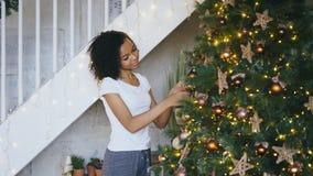 在家装饰圣诞树的卷曲混合的族种女孩为Xmas庆祝做准备 免版税库存照片