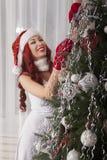 在家装饰圣诞树的圣诞老人女孩 美好微笑 图库摄影