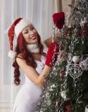 在家装饰圣诞树的圣诞老人女孩 美好微笑 免版税图库摄影