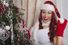 在家装饰圣诞树的圣诞老人女孩 美好微笑 库存照片