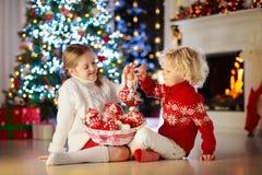 在家装饰圣诞树的孩子 小男孩和女孩被编织的毛线衣的有手工制造Xmas装饰品的 家庭庆祝 免版税库存照片