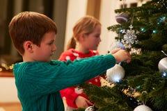 在家装饰圣诞树的孩子 免版税库存图片