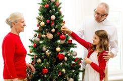 在家装饰圣诞树的微笑的家庭 免版税库存照片