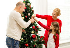 在家装饰圣诞树的微笑的家庭 免版税图库摄影