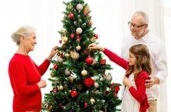 在家装饰圣诞树的微笑的家庭 库存图片
