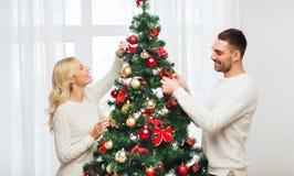 在家装饰圣诞树的愉快的夫妇 免版税图库摄影