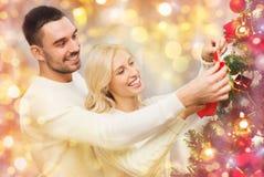 在家装饰圣诞树的愉快的夫妇 免版税库存图片