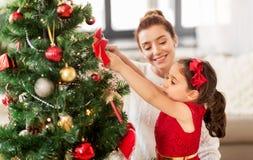 在家装饰圣诞树的愉快的家庭 免版税库存图片