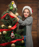 在家装饰新年树的美丽的女孩 免版税库存照片