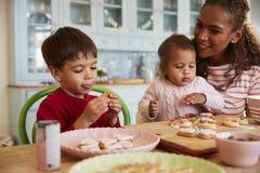 在家装饰曲奇饼的母亲和孩子一起 库存照片