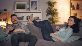 在家观看在电视的丈夫和妻子滑稽的影片一起笑和谈话 股票视频
