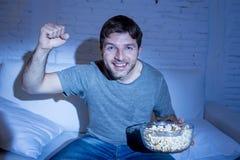 在家观看在电视的年轻愉快的人体育比赛欢呼他的打手势胜利拳头的队 免版税库存图片