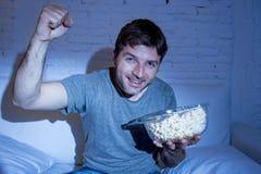 在家观看在电视的年轻愉快的人体育比赛欢呼他的打手势胜利拳头的队 免版税图库摄影