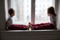 在家观看在窗口里的单独小男孩和女孩 库存图片