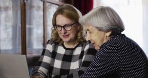 在家观看在膝上型计算机的两名资深妇女照片 股票视频