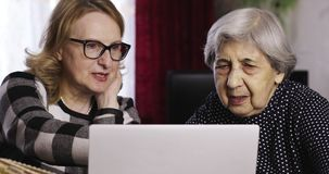 在家观看在膝上型计算机的两名资深妇女照片 影视素材