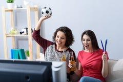 在家观看橄榄球的两个朋友 免版税库存照片