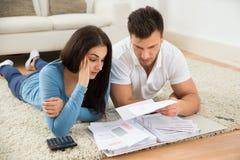 在家计算他们的票据的担心的年轻夫妇 免版税库存照片