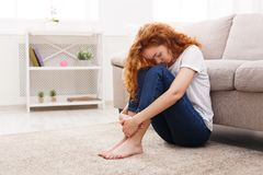 在家认为在地板上的哀伤的红头发人妇女 库存图片