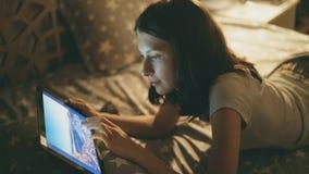 在家说谎在从旅行的床观看的照片的年轻微笑的妇女在数字式片剂计算机上在晚上 库存照片