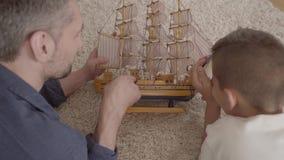 在家说谎在使用与船模特写镜头的蓬松地毯的地板上的父亲和他的儿子 儿童藏品 股票录像