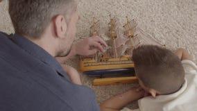 在家说谎在使用与船模特写镜头的蓬松地毯的地板上的父亲和他的儿子 家庭消费 股票录像