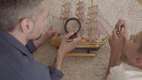 在家说谎在使用与船模特写镜头的蓬松地毯的地板上的父亲和他的儿子 看的人哦 股票录像