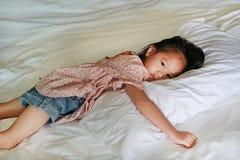 在家说谎在床上的亚裔矮小的中国女孩与看照相机 免版税库存照片