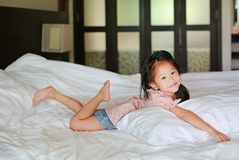 在家说谎在床上的亚裔矮小的中国女孩与看照相机 免版税库存图片