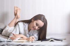 在家说谎在床卧室和写入日志或计划她的天的少妇,做日程表对明天 概念- r 库存照片