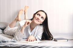 在家说谎在床卧室和写入日志或计划她的天的少妇,做日程表对明天 概念- r 免版税库存照片