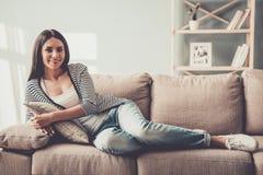 在家说谎在沙发的牛仔裤的年轻微笑的妇女 免版税库存照片