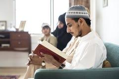 在家读从古兰经的穆斯林 免版税图库摄影
