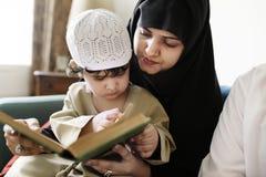 在家读从古兰经的穆斯林 免版税库存照片