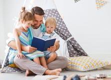 在家读对在帐篷的儿童图书的家庭父亲 免版税库存图片