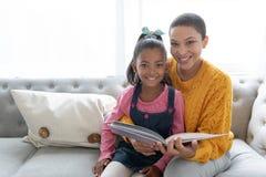 在家读故事书的母亲和女儿在一个沙发在客厅 库存图片