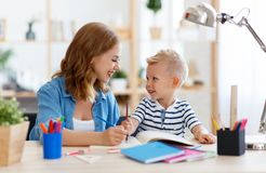 在家读母亲和儿童的儿子做家庭作业文字和 免版税图库摄影