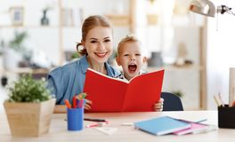 在家读母亲和儿童的儿子做家庭作业文字和 免版税库存图片