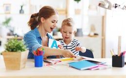 在家读母亲和儿童的儿子做家庭作业文字和 库存照片