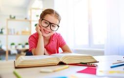 在家读滑稽的儿童的女孩做家庭作业文字和 免版税库存照片
